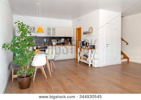 Modern Interior Of Cozy Kitchen, Dining Room, White Furniture, Wall, Black Accessories, Natural Mate