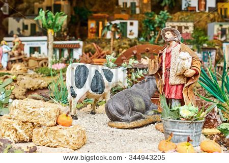 Candelaria, Tenerife, Spain - December 12, 2019: Detail of Christmas Belen -  Statuettes of people and houses in miniature depicting life of old town (Herder and cows)