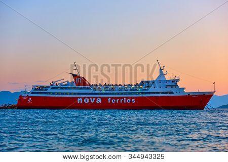 Aegina, Greece  - September 15, 2019: Ferryboat at the port of Aegina at twilight. Ship: Nova Ferries,