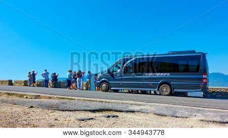Meteora, Kalambaka, Greece - September 18, 2019:  Group of tourists and bus for guided excursions at view point in Meteora