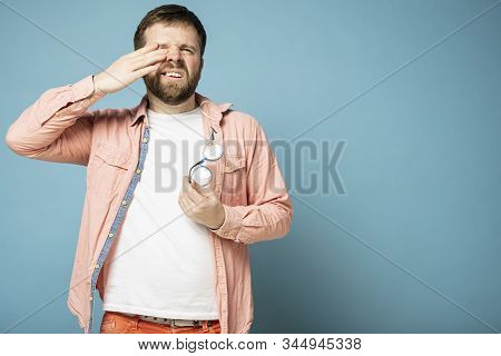 Man feels discomfort, took off glasses and rubs eyes. Copy space. poster