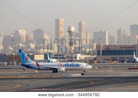 DUBAI, UAE - NOVEMBER 20, 2019: The Boeing B737 Emirates on Dubai International Airport with city skyline on a background. It is an major airline hub in the Middle East.