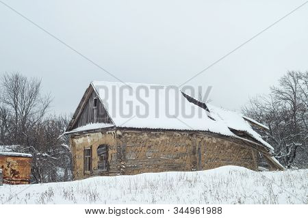 Abandoned Rustic Cold Old House With A Collapsed Roof. Winter Nature Of Secluded Countryside. Russia