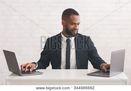 Black Businessman Typing On Two Laptops Over White Background, Productivity At Work