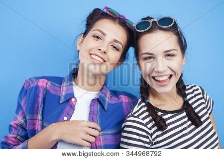 Lifestyle People Concept: Two Pretty Young School Teenage Girls Having Fun Happy Smiling On Blue Bac