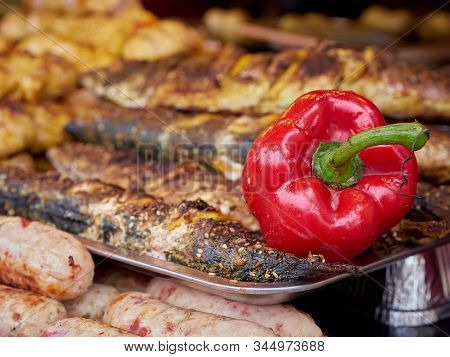 Red Grilled Meat Sausages Stack And Roasted Red Pepper On Trays At Street Food Festival, Selective F