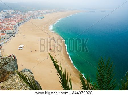 Portugal, Nazare Coastline View, Panoramic View Of Nazare Town, Blue Clouds On The Sky, White Sand O