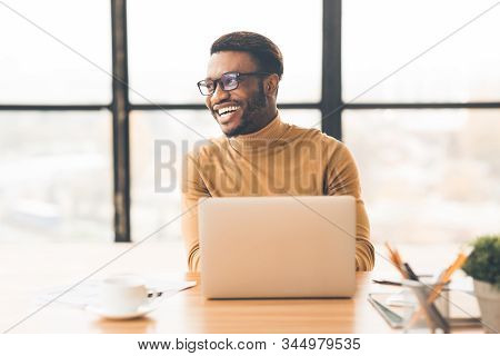 Success At Work. Happy Afro Businessman Sitting At Desk By Large Window In Modern Office, Looking As
