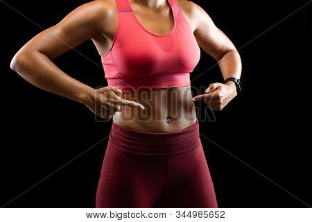 Sexy Body Of African Female Fitness Model Pointing At Her Abdominal Muscles Over Black Background, S