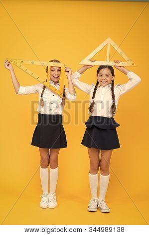 Bright Minds. Kids In Uniform At Yellow Wall. Friendship And Sisterhood. Happy Small Girls Study Mat