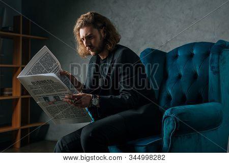 Tense Fashionable Businessman In Black Suit Reading Newspaper In Armchair In Dark