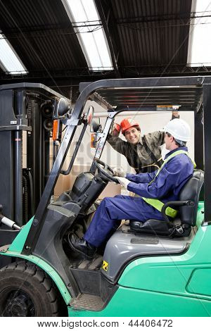 Forklift driver communicating with colleague at warehouse