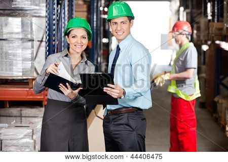 Portrait of supervisors with clipboard and foreman unloading cardboard boxes at warehouse
