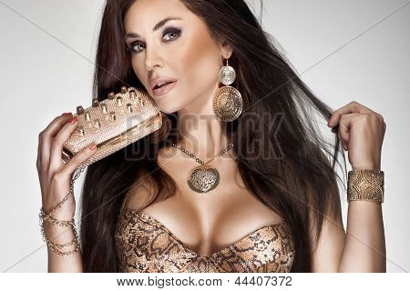 Beautiful Brunette Woman With Long Healthy Hair And Gold Jewellery.