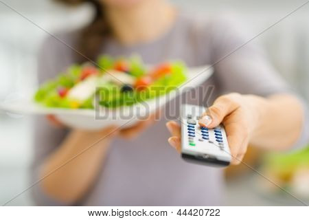 Closeup On Tv Remote Control And Fresh Salad In Hand Of Young Wo