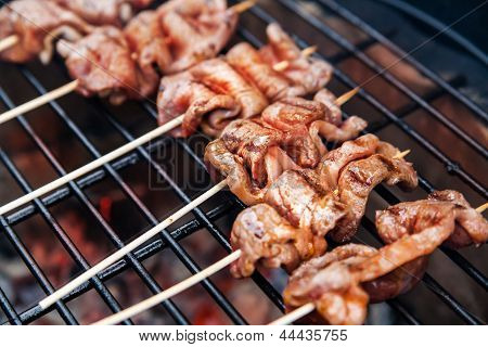 Meat rolls with bacon on grill