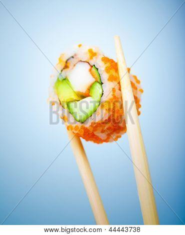 Lecker Sushi-Rolle mit Krabben, Gurken, Avocado und roter Kaviar in Stäbchen, die isoliert auf blau TERGRU