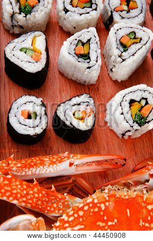 Roll with Cucumber , Cream Cheese with raw Tuna and Salmon inside. on wooden plate with live crab  . Isolated over white background . Japanese traditional Cuisine