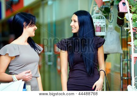 Two Beautiful Smiling Women Walking The Mall And Talking