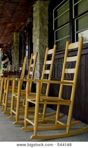 Row Of Yellow Rocking Chairs On Porch