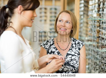 Happy senior woman with salesgirl selecting glasses in optician store