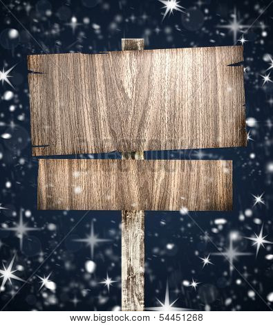 Old wooden signboard on background with snow, stars and bokeh. Christmas background