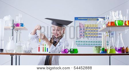Adorable little chemist posing in lab with flasks