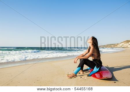 A beuatiful surfer girl making preparation for a surf session