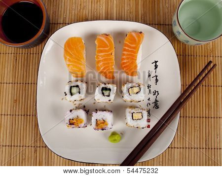 Fresh Sushi And Sashimi On A Plate With A Cup Of Sake And Chopsticks