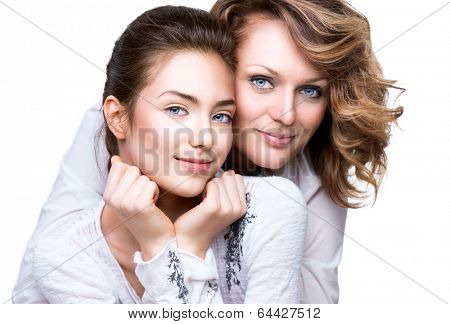 Mother and Teen Daughter. Close-up portrait of attractive happy mother and smiling teenage daughter isolated on a white background. Teenager girl with her mom