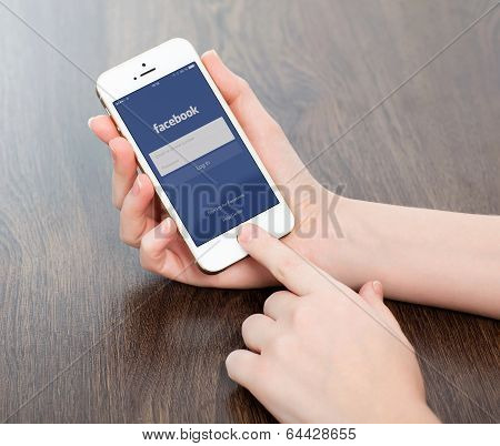 Female Hands Holding A White Iphone With Facebook On The Screen
