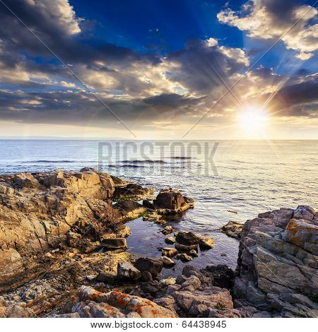 Calm Sea With Boulders On Coast At Sunset