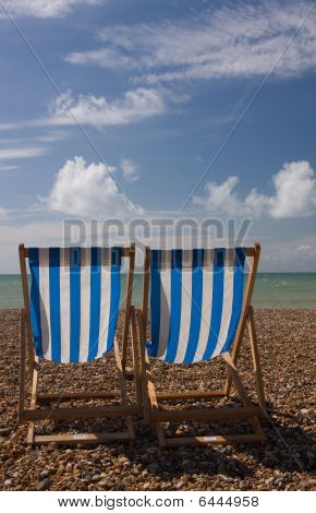 Pair Of Deck Chairs On Beach