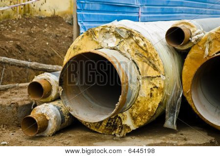 Multiple Rusty Metal Pipes With Yellow Heat Isolation.