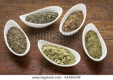 bowls of seaweed diet supplements (bladderwrack, sea lettuce, kelp, wakame and Irish moss) on a rustic wood table