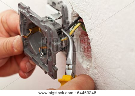 Electrician hands installing wires into electrical outlet - closeup poster