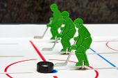 Three hockey players in line with puck poster