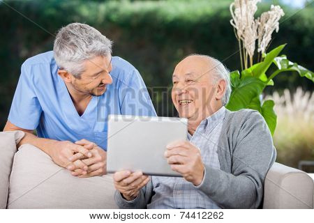 Male caretaker and senior man laughing while using tablet computer at nursing home porch