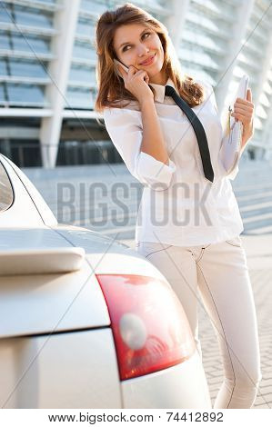 Beautiful young business woman with magazine talking on the phone. City business woman working.