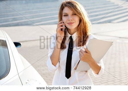 Successful businesswoman or entrepreneur talking on cellphone while walking outdoor. City business w