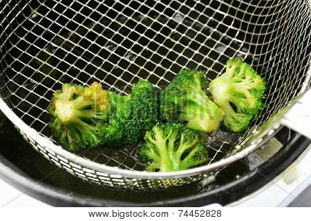 Broccoli in deep fryer, closeup