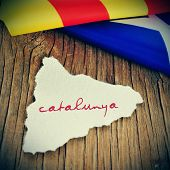 a piece of paper in the shape of Catalonia with the word Catalunya, Catalonia written in catalan, on a wooden background with an estelada flag in the background poster