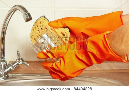 Hands in gloves with sponge and dirty cup over the sink in kitchen