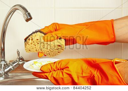 Hands in rubber gloves with sponge and dirty plate over the sink in kitchen