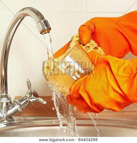 Hands in gloves wash the glass under running water in kitchen