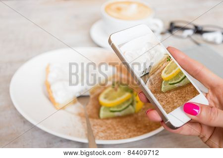 Woman taking photo of her cake in cafe with mobile phone poster