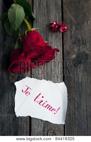 three red roses on wooden rustic table and hand written words je t'aime, meaning I love you poster