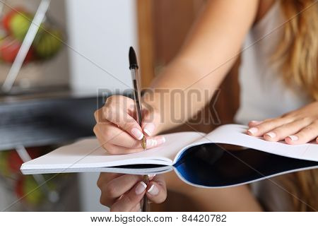 Woman Writer Hand Writing In A Notebook At Home