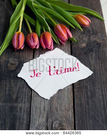 five bright tulips on a wooden rustic table and message je t'aime, meaning I love you poster