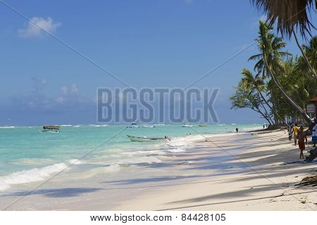 People walk by the tropical beach in Punto Cana, Dominican Republic.